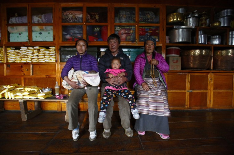 Nima Doma Sherpa, 25, whose husband Lakpa Sherpa, 26, died in the avalanche on April 18 2014, holds her daughter Pasang Choti Sherpa as she poses for a photograph with her father-in-law Tenzing Sherpa, 56, (center) and mother-in-law Chamchi Phuti Sherpa, 55, (right) inside their house in Khumjung approximately 3,700 meters above sea level in the Solukhumbu District on May 8, 2014. (REUTERS/Navesh Chitrakar)