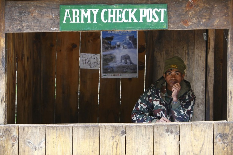 A Nepalese army personnel sits inside a check post as he waits to check permits for trekkers passing by, in the Solukhumbu District on April 26, 2014. (REUTERS/Navesh Chitrakar)
