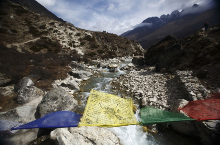 Prayer flags flutter over the Lobuche River on the way to Everest base camp near Pheriche, approximately 4,300 meters above sea level, in the Solukhumbu District on May 3, 2014. (REUTERS/Navesh Chitrakar)