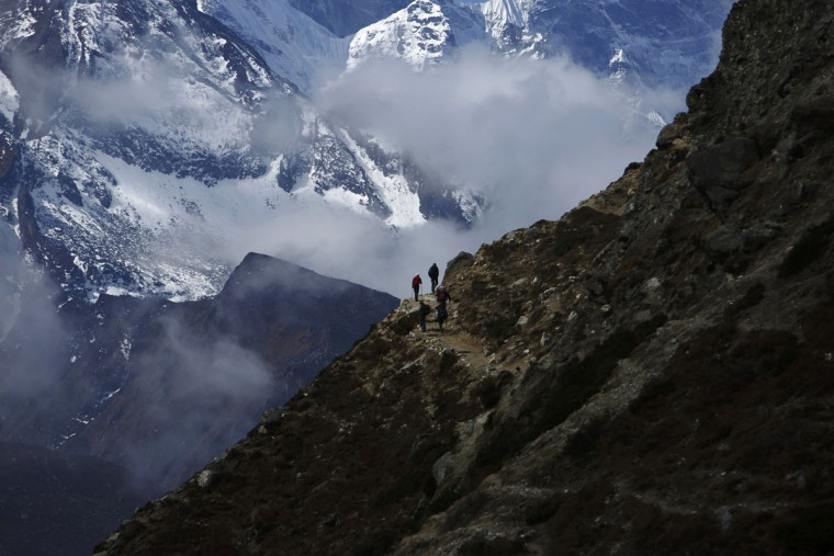 Trekkers walk in front of Mount Thamserku while on their way back from Everest base camp at Pheriche, approximately 4,300 meters above sea level, in the Solukhumbu District on May 3, 2014. (REUTERS/Navesh Chitrakar)