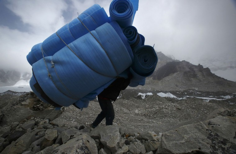 A porter carries mattresses back from Everest base camp, approximately 5,300 meters above sea level, in the Solukhumbu District on May 6, 2014. (REUTERS/Navesh Chitrakar)