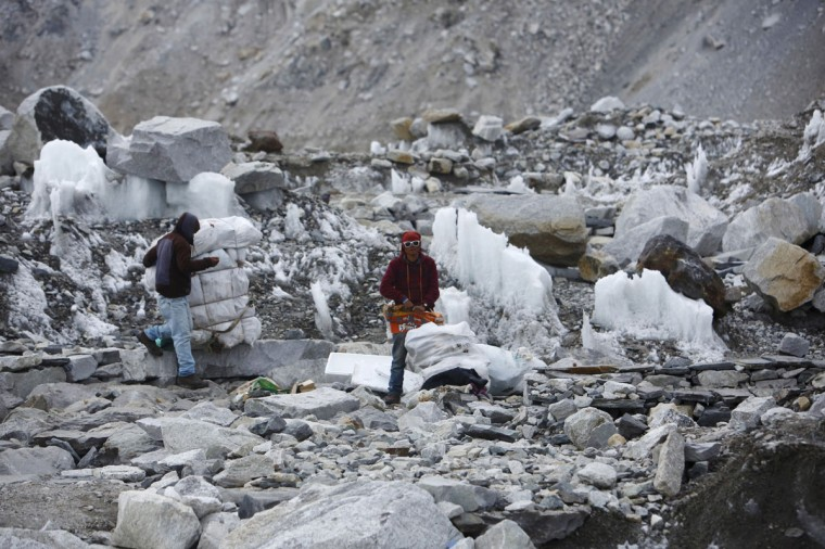 Garbage collectors collect rubbish at the deserted Everest base camp, approximately 5,300 meters above sea level, in Solukhumbu District on May 6, 2014. (REUTERS/Navesh Chitrakar)