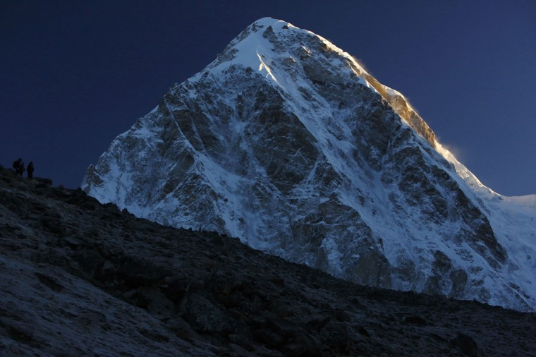 Light from a sunrise illuminates Mount Pumori, which is approximately 7,100 meters high, as trekkers look at the mountains from Kala Patthar in the Solukhumbu District on May 7, 2014. (REUTERS/Navesh Chitrakar)