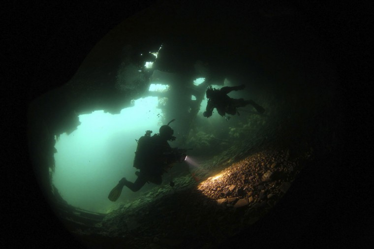 Divers explore inside the upturned blockship Tabarka in Burra Sound, in the Orkney Islands, Scotland on May 8, 2014. Tabarka was deliberately sunk during WWII to try and block the path of German U-Boats. (REUTERS/Nigel Roddis)