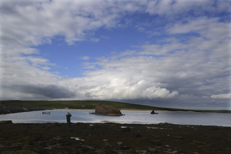 A man takes a photograph of a blockship in the Orkney Islands, Scotland May 8, 2014. A blockship is a boat that has been sunk in order to block a waterway. (REUTERS/Nigel Roddis)