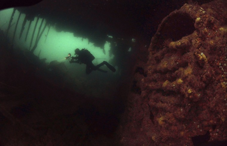A diver swims past the boilers of the upturned blockship Tabarka in Burra Sound, in the Orkney Islands, Scotland on May 8, 2014. Tabarka was deliberately sunk during WWII to try and block the path of German U-Boats. (REUTERS/Nigel Roddis)