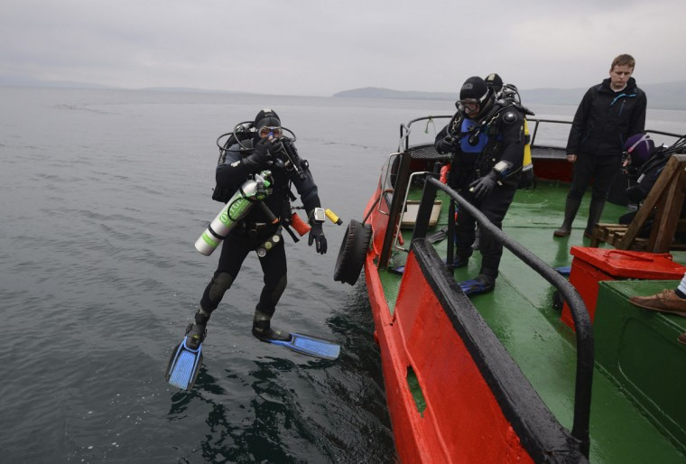 A diver jumps into the water, ahead of a dive on the wreck of a German WWI warship at Scapa Flow in the Orkney Islands, Scotland on May 7, 2014. (REUTERS/Nigel Roddis)