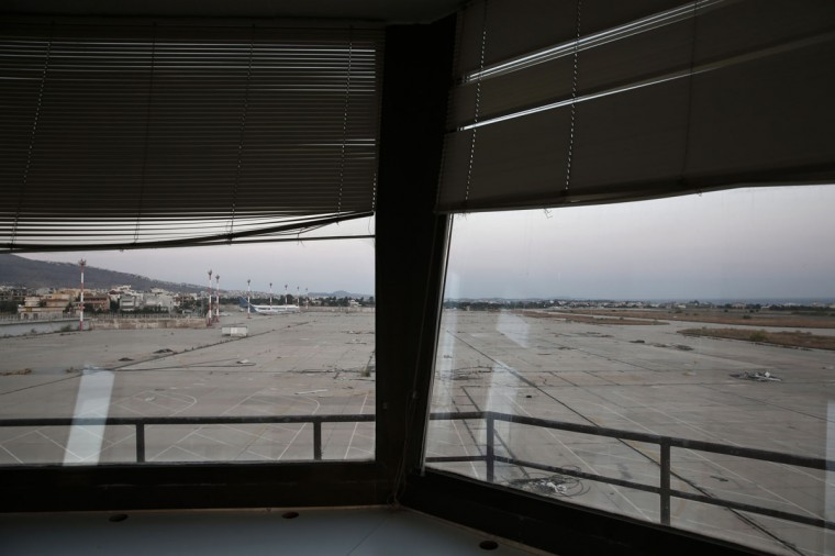 A plane is seen through the window of an auxiliary control tower at the former Athens International airport, Hellenikon. (REUTERS/Yorgos Karahalis)