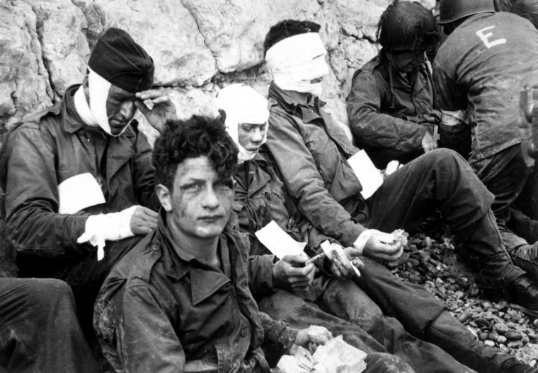 American assault troops of the 16th Infantry Regiment, injured while storming Omaha Beach, wait for the Chalk Cliffs for evacuation to a field hospital for further medical treatment in this photo taken at Collville-sur-Mer, Normandy, France, on June 6, 1944. (via Reuters)