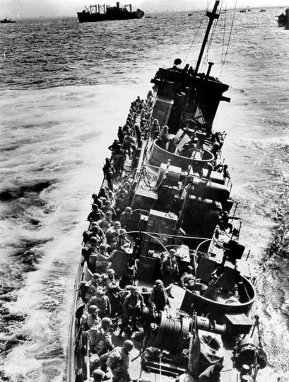 The Coast Guard LCI(L)-85, battered by enemy fire after approaching Omaha Beach, prepares to evacuate the troops to the U.S.S. Samuel Chase. She sank shortly after this photograph was taken. The LCI (L)-85 was one of four Coast Guard LCI's that were destroyed on D-Day. (Via Reuters)