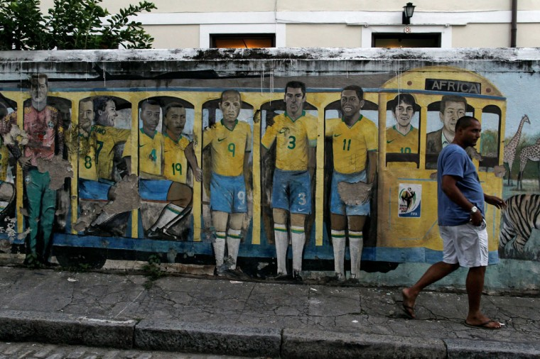 "A man walks past graffiti depicting Brazilian soccer players, who took part in the 2010 World Cup soccer tournament, inside a typical Brazilian railway wagon, known as a ""bondinho"" in Portugese, on a street in Rio de Janeiro May 11, 2013. (REUTERS/Pilar Olivares)"