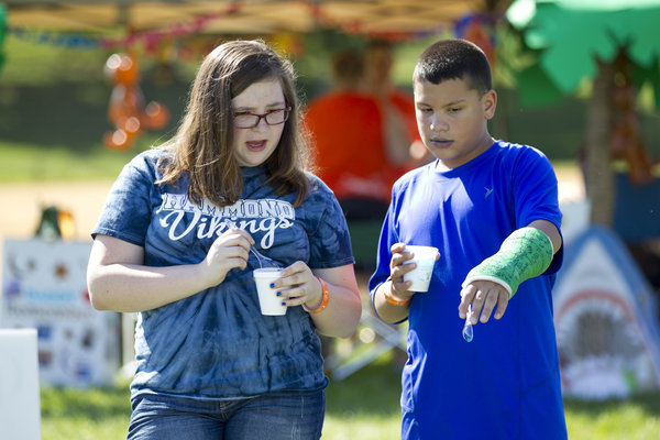 Juliana Belt, left, 12, and Jose Gutierrez, 12, both of Laurel, look at the luminaria surrounding the track at the Relay for Life. (Jen Rynda, Baltimore Sun Media Group)