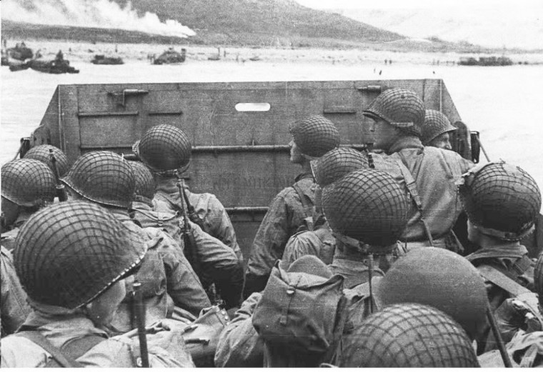American assault troops huddle behind the protective bow of a landing craft on June 6, 1944 as it nears a beachhead on the northern coast of France during World War II. The smoke rising in the background is naval gunfire supporting the D-Day landing. (US Army photo)