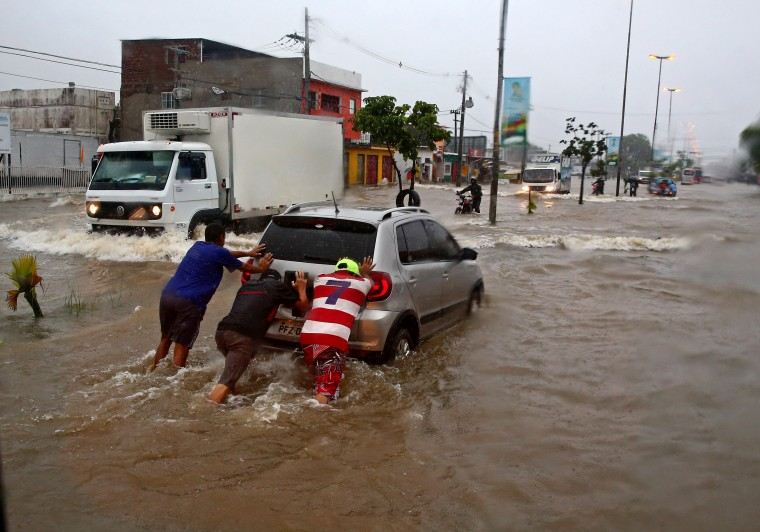 Three men push a car through the flooded streets of Recife during heavy rains prior to the match between USA against Germany during the 2014 World Cup at Arena Pernambuco. (Mark J. Rebilas-USA TODAY Sports)
