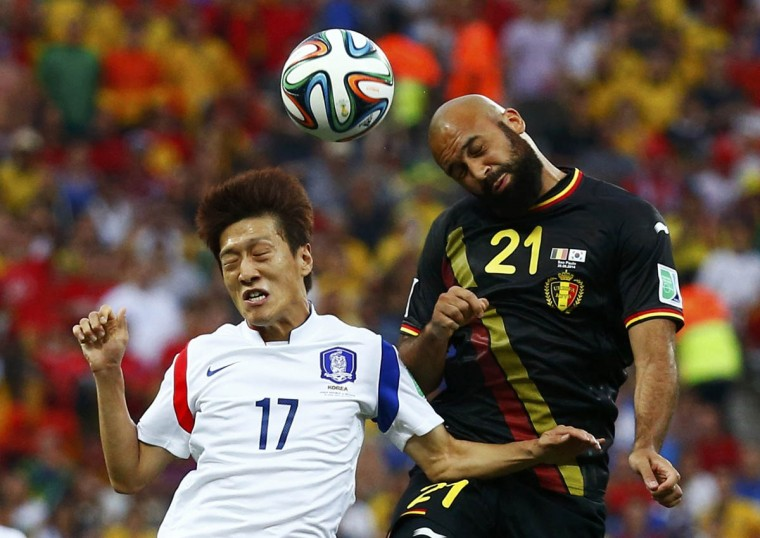 South Korea's Lee Chung-yong (Left) jumps for the ball with Belgium's Anthony Vanden Borre during their 2014 World Cup Group H soccer match at the Corinthians arena in Sao Paulo June 26, 2014. (Paul Hanna/Reuters photo)