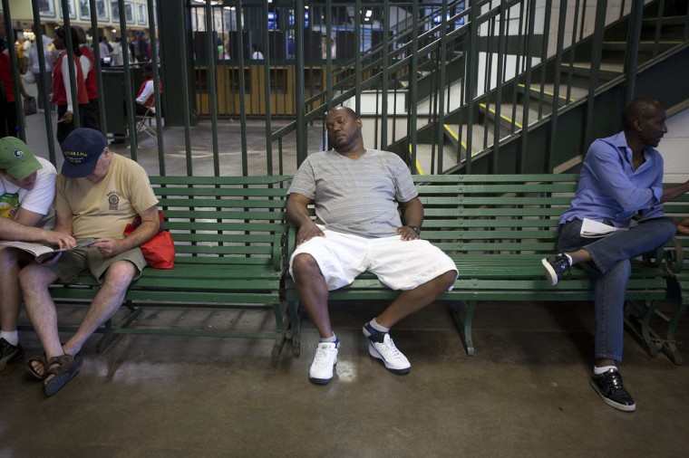 A man takes a nap on a bench in the grandstand before the 2014 Belmont Stakes in Elmont, New York June 7, 2014. (REUTERS/Carlo Allegri)