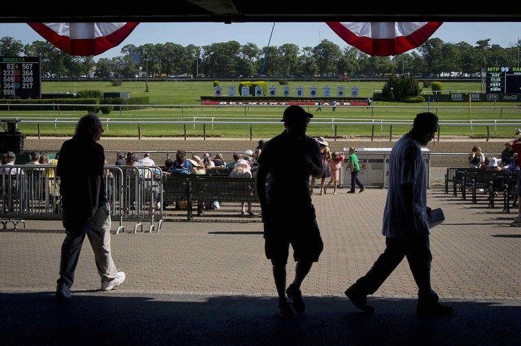People walk under the grandstand before the 2014 Belmont Stakes in Elmont, New York June 7, 2014. (REUTERS/Carlo Allegri)
