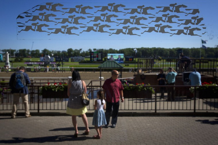 Horseracing stickers are pictured on a window of the grandstand as people walk past, before the 2014 Belmont Stakes in Elmont, New York June 7, 2014. (REUTERS/Carlo Allegri)