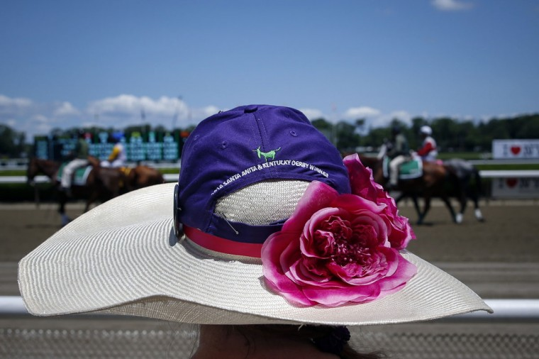 A woman stands on the rail as horses make their way for the third race at Belmont Park before the 2014 Belmont Stakes in Elmont, New York June 7, 2014. (REUTERS/Shannon Stapleton)