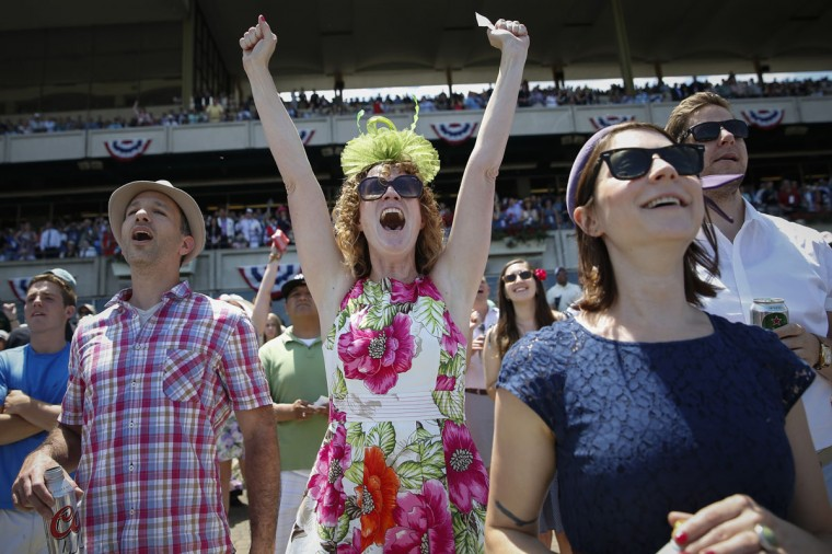 Shayna Reade (C) cheers as horses cross the finish line during the third race at Belmont Park before the 2014 Belmont Stakes in Elmont, New York June 7, 2014. (REUTERS/Shannon Stapleton)