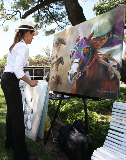 Artist Susan Sommer-Luarca paints a portrait of the past three triple crown winners before the 2014 Belmont Stakes at Belmont Park. (Brian Spurlock-USA TODAY Sports)