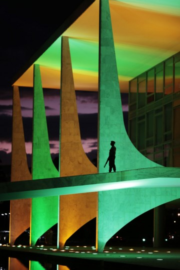 A security guard walks in front of the Planalto Palace as it is lit up in the colors of the Brazilian national flag ahead of the 2014 World Cup, in Brasilia on June 5, 2014. (REUTERS/Ueslei Marcelino)