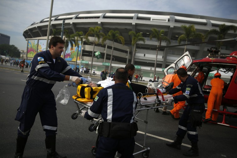Public security workers transport a person acting as a casualty into a helicopter during an evacuation drill in front of the Maracana stadium in Rio de Janeiro on June 7, 2014. The 2014 World Cup soccer tournament will be held in 12 cities in Brazil from June 12 to July 13. (REUTERS/Pilar Olivares)