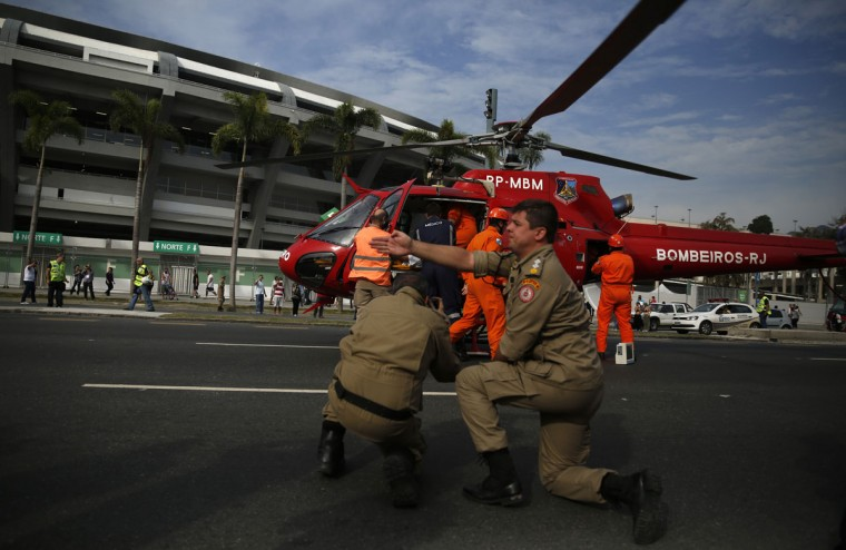 Public security workers transport a person acting as a casualty into a helicopter during an evacuation drill in front of the Maracana stadium in Rio de Janeiro on June 7, 2014. (REUTERS/Pilar Olivares)