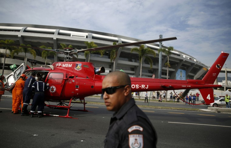 Public security workers stand near a helicopter as they take part in a drill to evacuate an injured person in front of the Maracana stadium in Rio de Janeiro on June 7, 2014. The 2014 World Cup soccer tournament will be held in 12 cities in Brazil from June 12 to July 13. (REUTERS/Pilar Olivares)