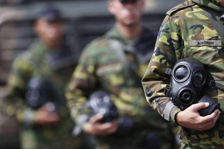 A soldier holds a gas mask during a event by members of the Brazilian Army, Navy and Air Force presenting Defense and Security personnel and equipment that will be used during the 2014 World Cup in Brasilia, on June 8, 2014. (REUTERS/Ueslei Marcelino)