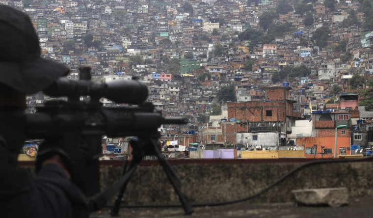 A sniper aims his gun to Rocinha slum during the inauguration of its Peacekeeping Unit Program (UPP) in Rio de Janeiro on September 20, 2012. (REUTERS/Ricardo Moraes)