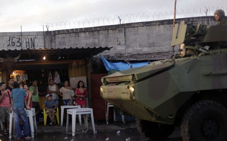 Residents watch as Brazilian Navy soldiers in an armored vehicle patrol the Mare slums complex in Rio de Janeiro, on April 5, 2014. (REUTERS/Ricardo Moraes)