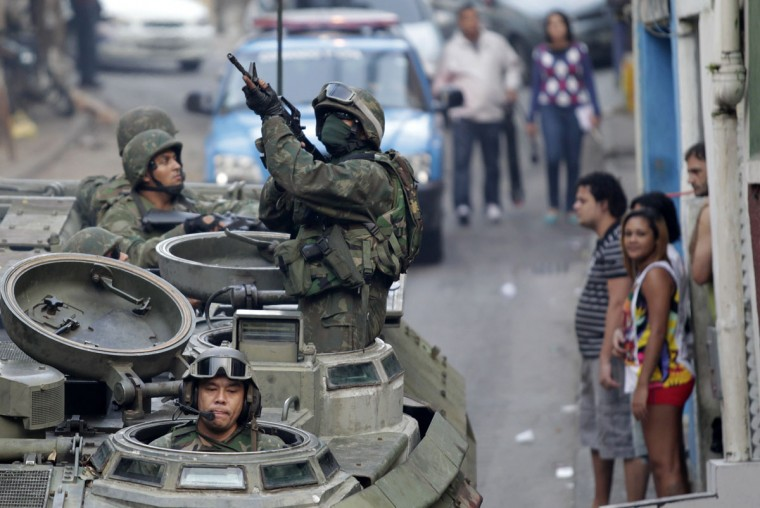 Brazilian Navy soldiers patrol in an armoured vehicle during an operation against drug dealers at Mangueira slum in Rio de Janeiro June 19, 2011. Rio de Janeiro's security forces started a big operation in Mangueira slum to base a peacekeeping unit near Maracana Stadium. It is the last favela, located near Maracana Stadium, which was introduced to the peace program to ensure the security of the 2014 World Cup. (REUTERS/Ricardo Moraes)
