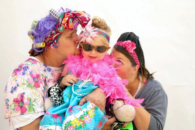 Bella Reichert, 3, gets kisses from her parents. (Shan Gordon/Special to The Baltimore Sun)