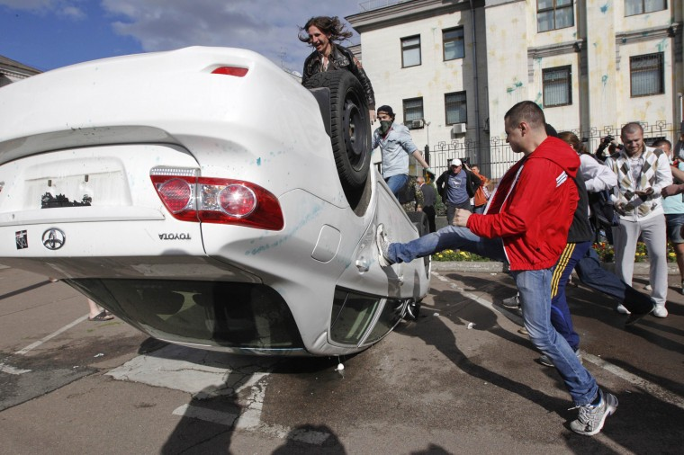 Pro-Ukrainian protestors overturn a car during a rally in front of the Russian embassy in Kiev. The rally was held to demand Russian authorities and President Vladimir Putin to stop supporting groups of separatists in eastern Ukraine, according to the protesters. (Valentyn Ogirenko/Reuters)
