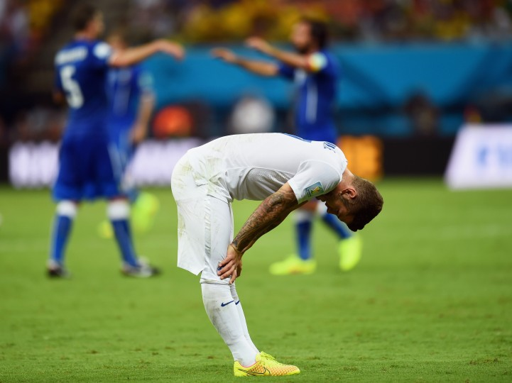 A dejected Jack Wilshere of England looks down as Italy celebrate defeating England 2-1 during the 2014 FIFA World Cup Brazil Group D match between England and Italy at Arena Amazonia in Manaus, Brazil. (Christopher Lee/Getty Images)