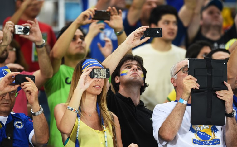 Fans look on with electronic devices during the 2014 FIFA World Cup Group F match between Nigeria and Bosnia-Herzegovina at Arena Pantanal in Cuiaba, Brazil. (Stu Forster/Getty Images)