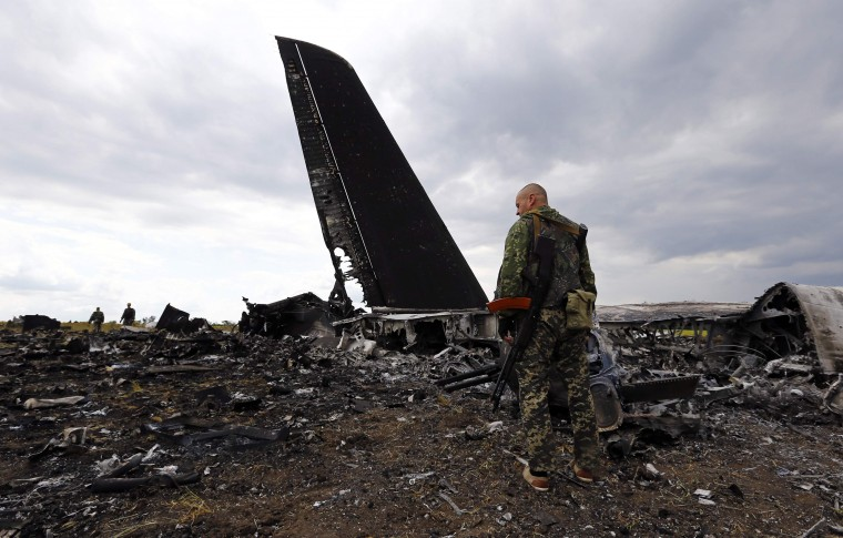 Pro-Russian separatists walk search the crash site of a Ukrainian Il-76 transport plane shot down at an airport in Luhansk. Pro-Russian launched an anti-aircraft missileat the army transport as it came in for a landing, killing all 49 military personnel on board. (Shamil Zhumatov/Reuters)