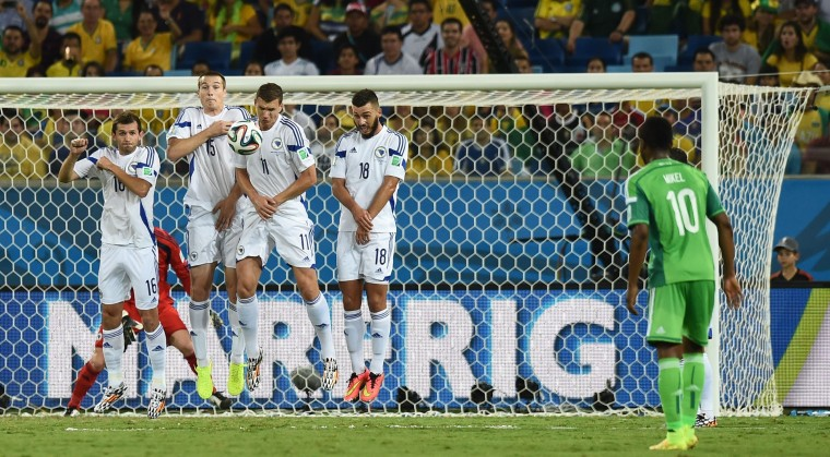 Players for Bosnia-Hercegovina's jump to block a free kick by Nigeria's midfielder John Obi Mikel (R) during the Group F football match between Nigeria and Bosnia-Hercegovina at the Pantanal Arena in Cuiaba during the 2014 FIFA World Cup. (Jewel Samad/AFP-Getty Images)