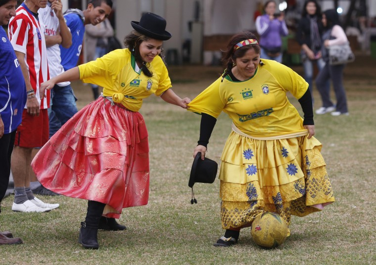 Andean women wearing Brazil-themed jerseys play soccer at a market in Lima. As the vendors at a craft market in the district of La Molina in Lima, the women played soccer during an event to promote their shops. (Mariana Bazo/Reuters)