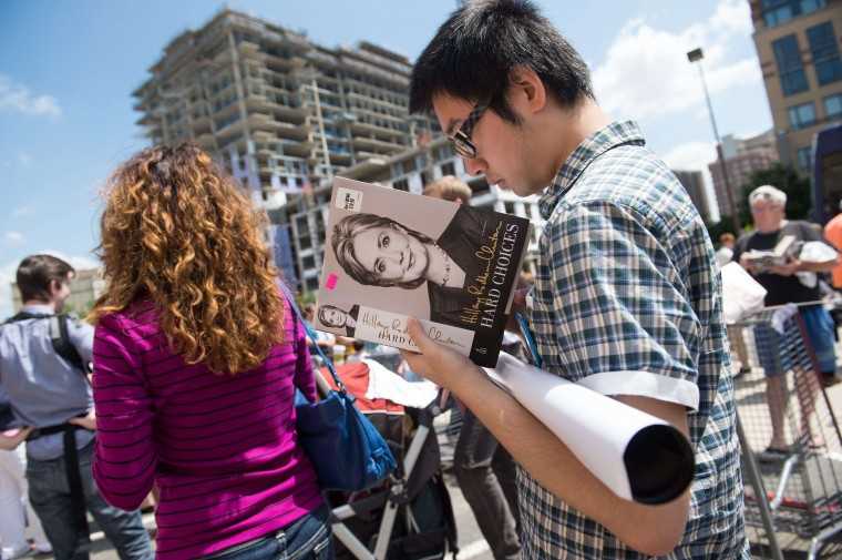 "A man reads from Secretary of State Hillary Clinton's new book ""Hard Choices"" while in line outside an Arlington, Va., Costco. Clinton is widely thought to be mulling a run for the 2016 presidential election. (Nicholas Kamm/AFP-Getty Images)"