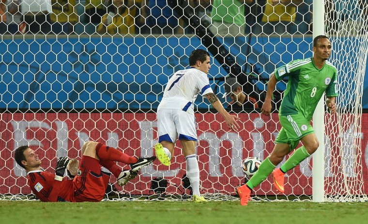 Bosnia-Hercegovina's goalkeeper Asmir Begovic (L) concedes a goal to Nigeria's forward Peter Odemwingie (R) during the Group F football match between Nigeria and Bosnia-Hercegovina at the Pantanal Arena in Cuiaba during the 2014 FIFA World Cup. (Jewel Samad/AFP-Getty Images)