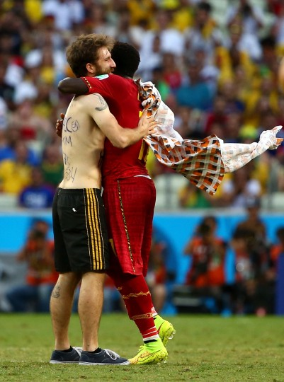 A pitch invader hugs Sulley Muntari of Ghana during the 2014 FIFA World Cup Brazil Group G match between Germany and Ghana at Castelao in Fortaleza, Brazil. (Robert Cianflone/Getty Images)
