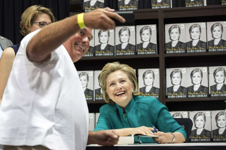 "A man takes a picture of himself and former U.S. Secretary of State Hillary Clinton as she signs copies of her book ""Hard Choices"" at a Costco Arlington, Va. (Joshua Roberts/Reuters)"