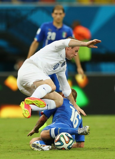 Wayne Rooney of England jumps over Daniele De Rossi of Italy during the 2014 FIFA World Cup Brazil Group D match between England and Italy at Arena Amazonia in Manaus, Brazil. (Elsa/Getty Images)