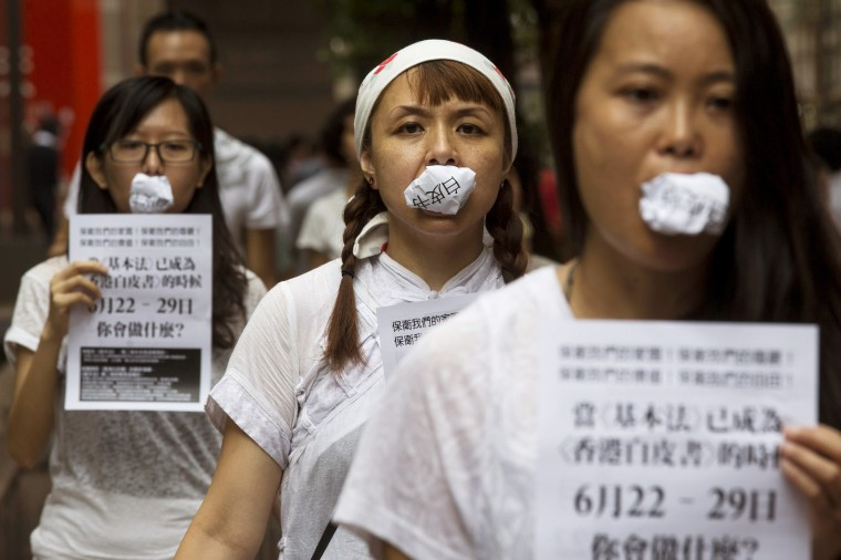 """Local artists bite photo copies of the white paper """"One country, two systems,"""" released earlier by Beijing on Hong Kong's control, to symbolize people's speech has been disregarded and to urge people to vote in an unofficial referendum in Hong Kong. More than 200,000 people voted for full democracy in Hong Kong within the first few hours of an unofficial online referendum in a civil campaign that has sparked warnings from China's Communist Party leaders. (Tyrone Siu /Reuters)"""