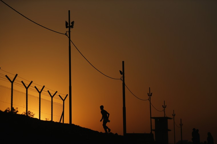 A man walks through a Kurdish checkpoint at sunset near a temporary displacement camp in Kalak, Iraq. Thousands of people have fled Iraq's second city of Mosul after it was overrun by ISAS (Islamic State of Iraq and Syria) militants. Many have been temporarily housed at various displaced persons camps around the region including the area close to Erbil, as they hope to enter the safety of the nearby Kurdish region. (Dan Kitwood/Getty Images)