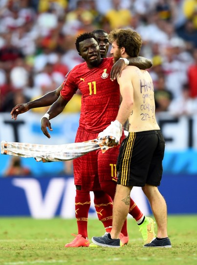 A pitch invader hugs Sulley Muntari of Ghana during the 2014 FIFA World Cup Brazil Group G match between Germany and Ghana at Castelao in Fortaleza, Brazil. (Laurence Griffiths/Getty Images)