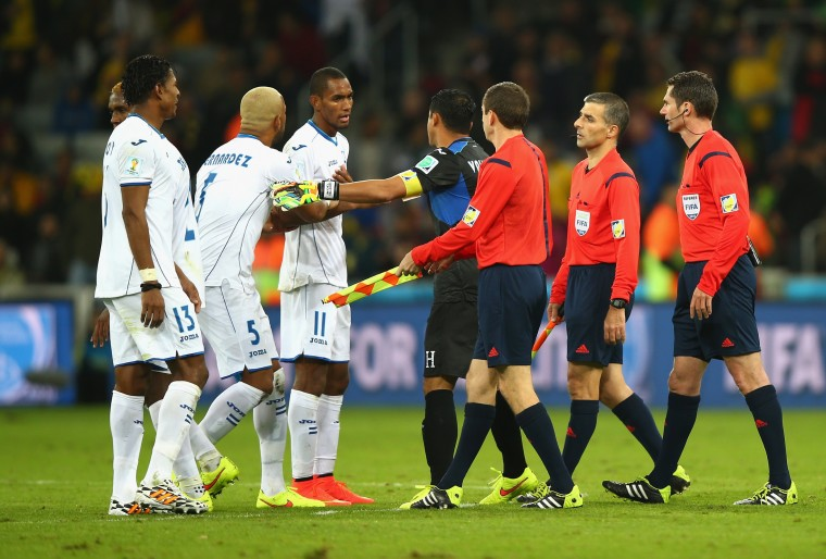 Jerry Bengtson of Honduras (3rd L) is held back by teammates as referee Benjamin Williams (R) and assistant referees walk off the field at the half during the 2014 FIFA World Cup Brazil Group E match between Honduras and Ecuador at Arena da Baixada in Curitiba, Brazil. (Clive Rose/Getty Images)