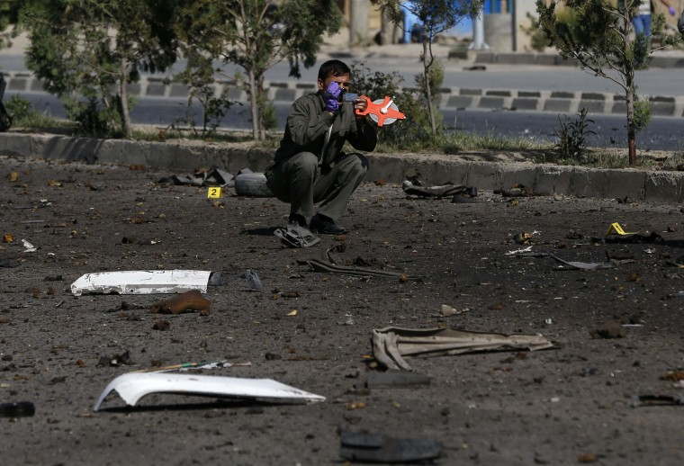 An investigator at the site of a bomb attack in Kabul. A suicide bomber in western Kabul targeted top High Peace Council advisor Mohammad Massom Stanikzai on Saturday, police said, killing one civilian and injuring several others. (Omar Sobhani/reuters)